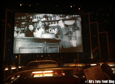 The large movie screen at Sci-Fi Dine-in Theater plays B-movie clips